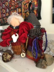 woven doll with gray hair, colorful red shawl, necklace and jewels of volcano power