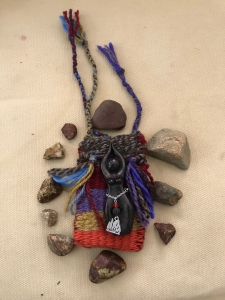 woven colorful small bag surrounded by stones & a volcano goddess figuring